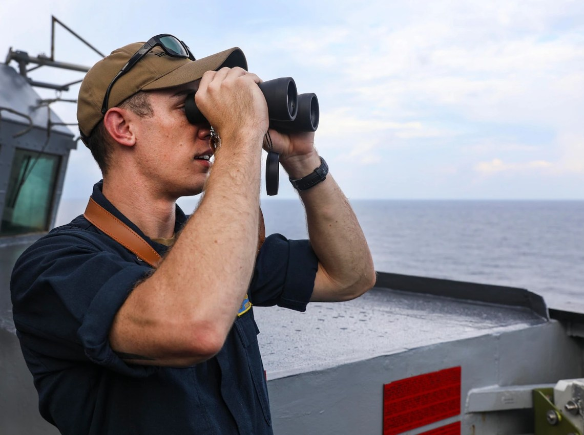 Lt.j.g. Andrew Hayne, from Parker, Colo., uses binoculars to monitor a surface contact from the bridge wing of the Arleigh Burke-class guided-missile destroyer USS Benfold (DDG 65) while conducting routine underway operations. Benfold is forward-deployed to the U.S. 7th Fleet area of operations in support of a free and open Indo-Pacific.