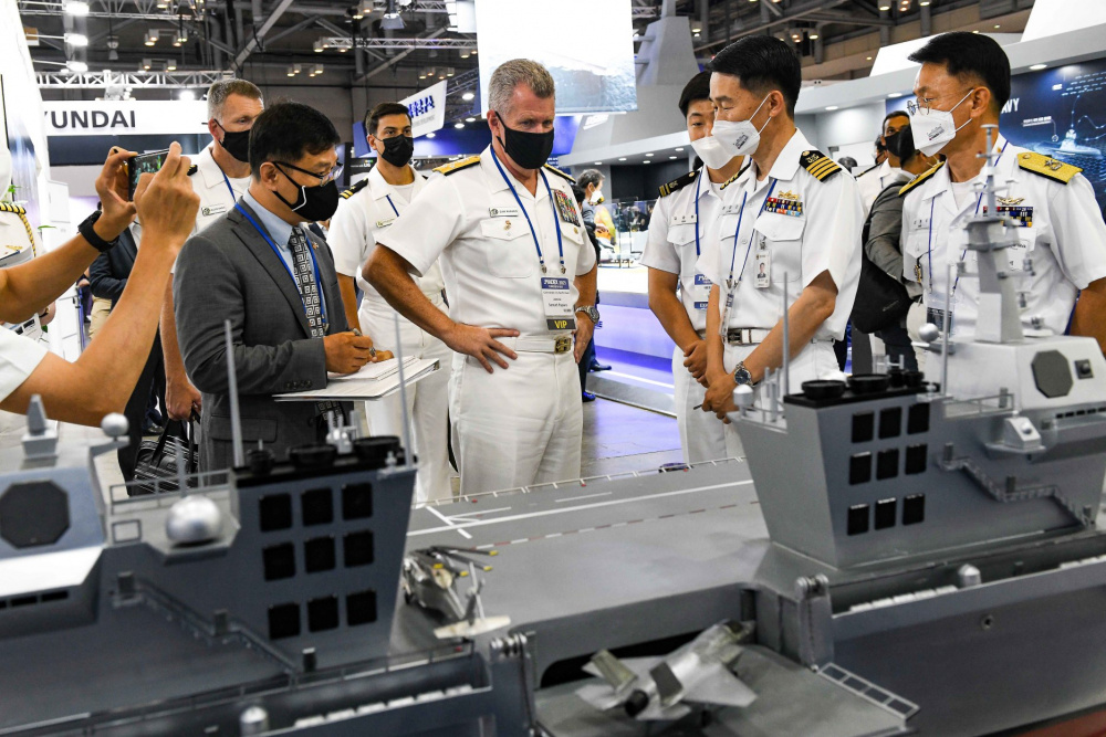 Adm. Samuel Paparo, Commander, U.S. Pacific Fleet, receives a brief about the Republic of Korea Navy's future light aircraft carrier program during a tour of the International Maritime Defense Industry Exhibition in Busan, Republic of Korea.