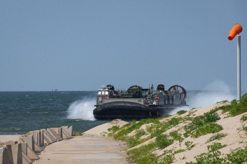 A U.S. Navy landing craft, air cushion lands on a beach while carrying tactical vehicles during Defense Support of Civil Authorities (DSCA) mission rehearsals at Naval Base Norfolk, Virginia, July 22, 2021.
