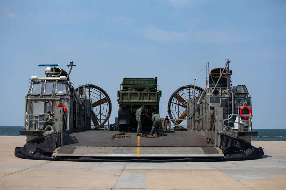 U.S. Navy Sailors unload tactical vehicles from an air cushion, landing craft onto a vehicle staging area during Defense Support of Civil Authorities (DSCA) mission rehearsals at Naval Base Norfolk, Virginia, July 22, 2021.