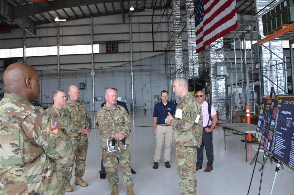 Lt. Col. Dan Thetford, right, Product Manager for the UH-60V Black Helicopter, provides an overview of the aircraft capabilities to Brig. Gen. Andy Chevalier, center, Land Component Commander, Rohde Island National Guard, and several state aviation officers at the Huntsville, Al. International Airport July 13.