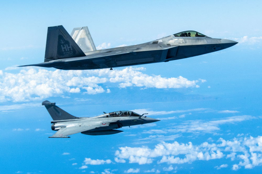 A Hawaii Air National Guard F-22 Raptor flies in formation with a French Air and Space Force F3-R Rafale June 30, 2021, near Oahu, Hawaii.