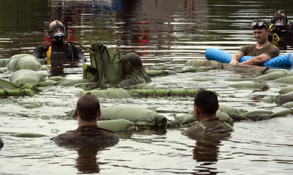 Soldiers from 2nd Battalion 501st Parachute Infantry Regiment participating in testing the Parachutist Flotation Device undergo combat water survival training at Fort Bragg, North Carolina's Mott Lake.