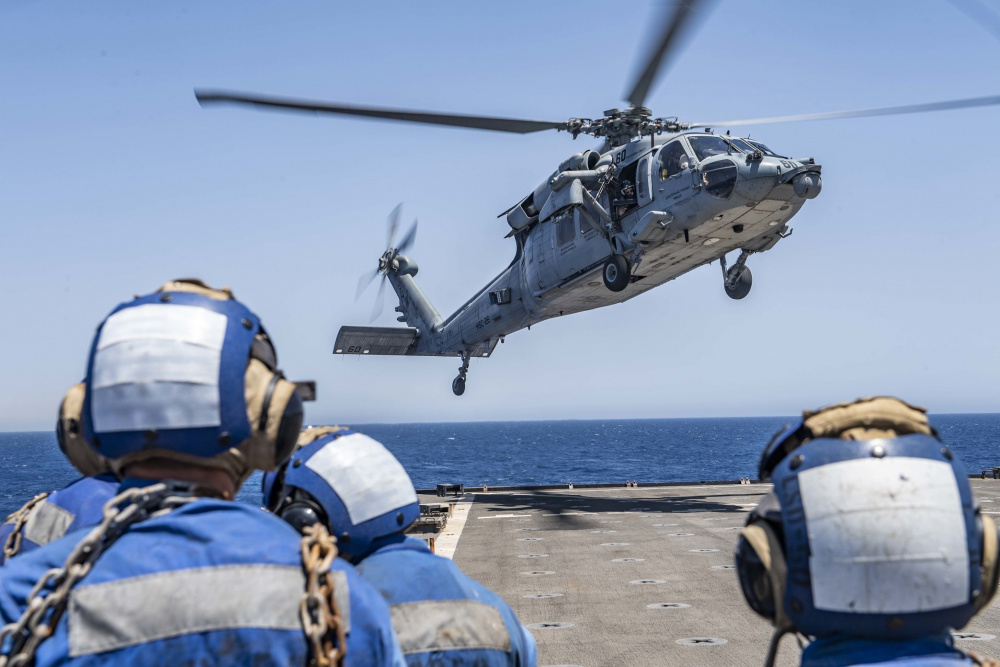 """An MH-60S Sea Hawk helicopter attached to the """"Chargers"""" of Helicopter Sea Combat Squadron (HSC) 26 approaches the flight deck of the Harpers Ferry-class dock landing ship USS Carter Hall (LSD 50), June 19."""