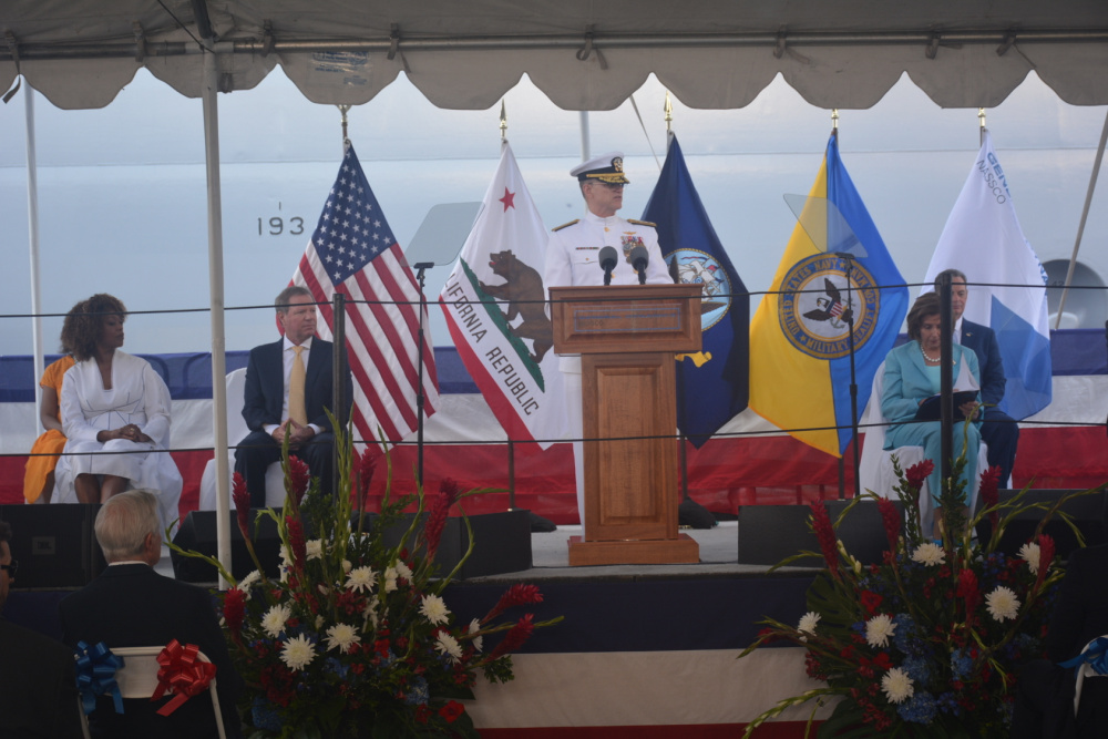 Rear Adm. Michael Wettlaufer, Commander, Military Sealift Command, speaks during the christening ceremony of the fleet replenishment oiler USNS John Lewis. Wettlaufer was one of several speakers at the event that also included House Speaker Nancy Pelosi (right) and actress and activist Alfre Woodard Spenser (left).