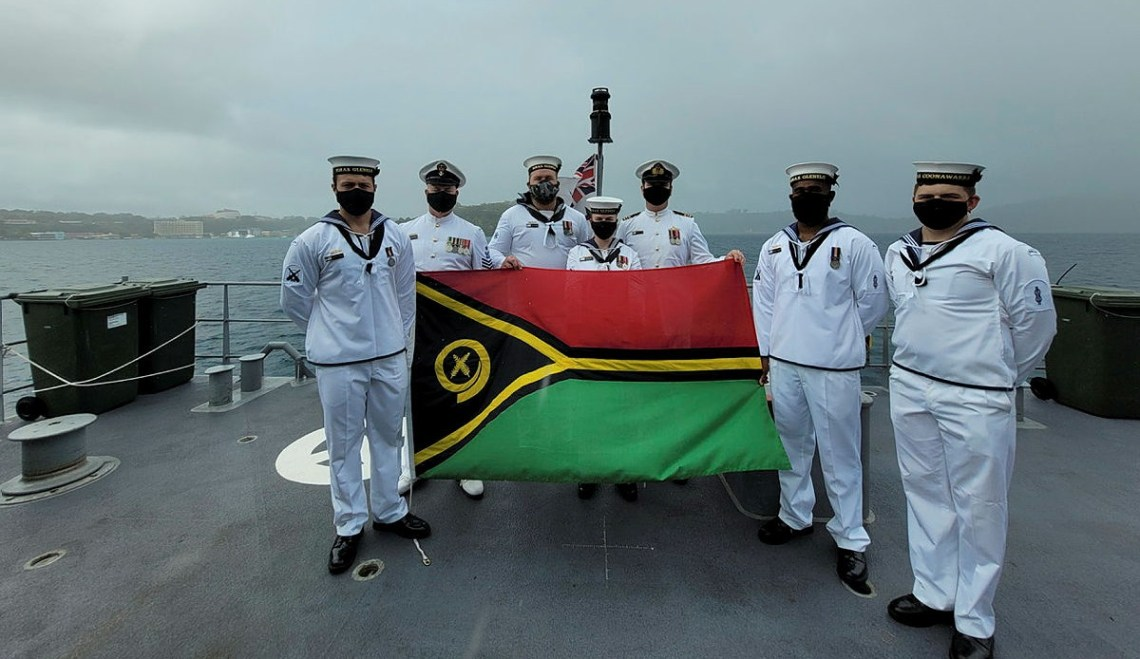 Able Seaman Boatswain's Mate Marcus Dawson, Petty Officer Boatswains Stephen Harvey, Leading Seaman Naval Police Coxswain Jack Williams, Leading Seaman Communications and Information Systems Kiani Hughes, Commanding Officer of HMAS Glenelg Lieutenant Commander LCDR Alexander Finnis, Able Seaman Boatswain's Mate Ebrahim Dollie, Able Seaman Marine Technician Christopher Barnett display the Vanuatu National Flag in celebration of Vanuatu's Independence Day while at anchor in Port Vila Harbour.