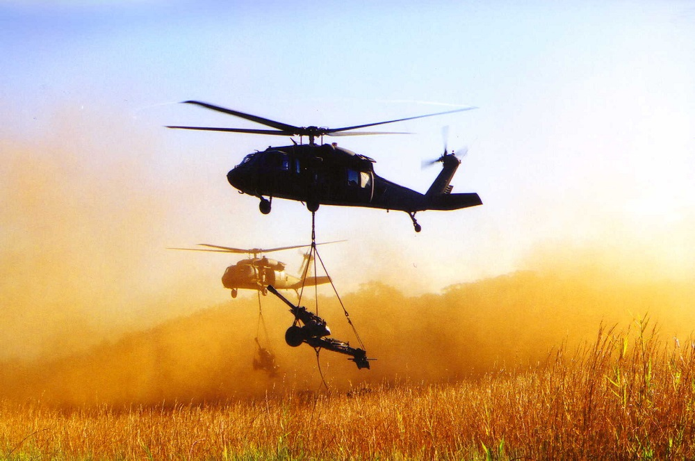 M119A1 light towed howitzer slingloaded by UH-60 Blackhawk Helicopters