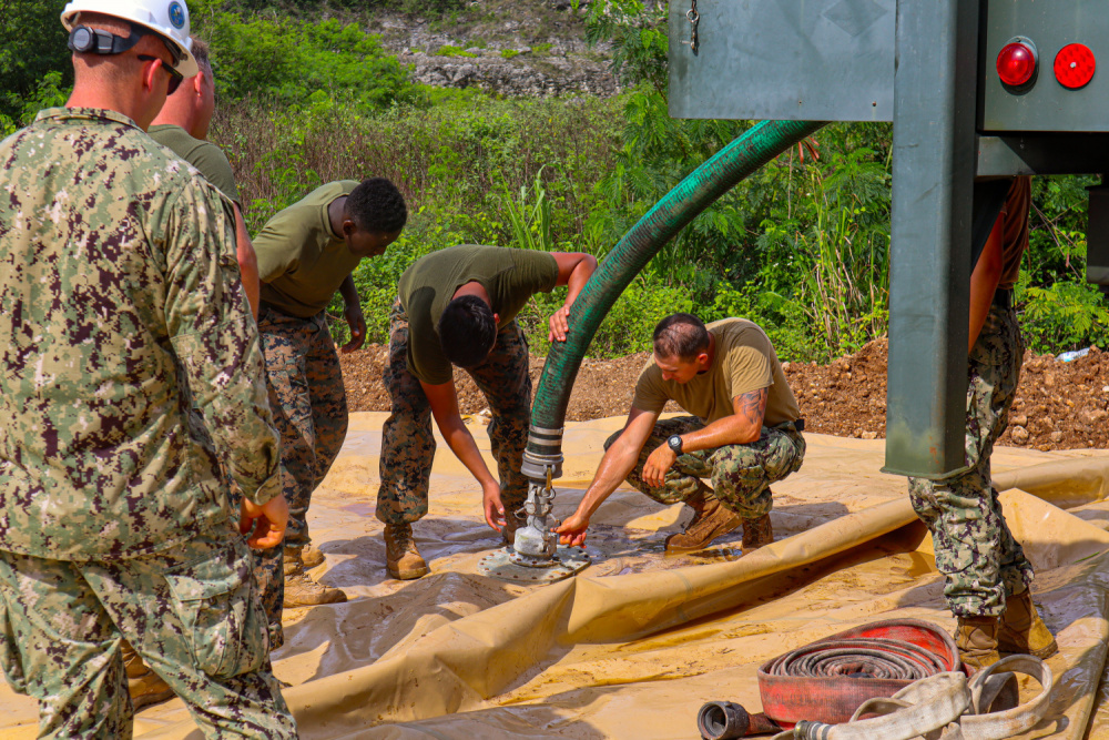 Seabees assigned to Naval Mobile Construction Battalion (NMCB) 11 Det. Guam operate a Medium Tactical Vehicle Replacement MK28C to fill a bladder for a chemical treatment mixture while supporting III MEF to establish a prototype Landing Zone using a biocement application system developed by bioMASON with support from Defense Advanced Research Projects Agency.