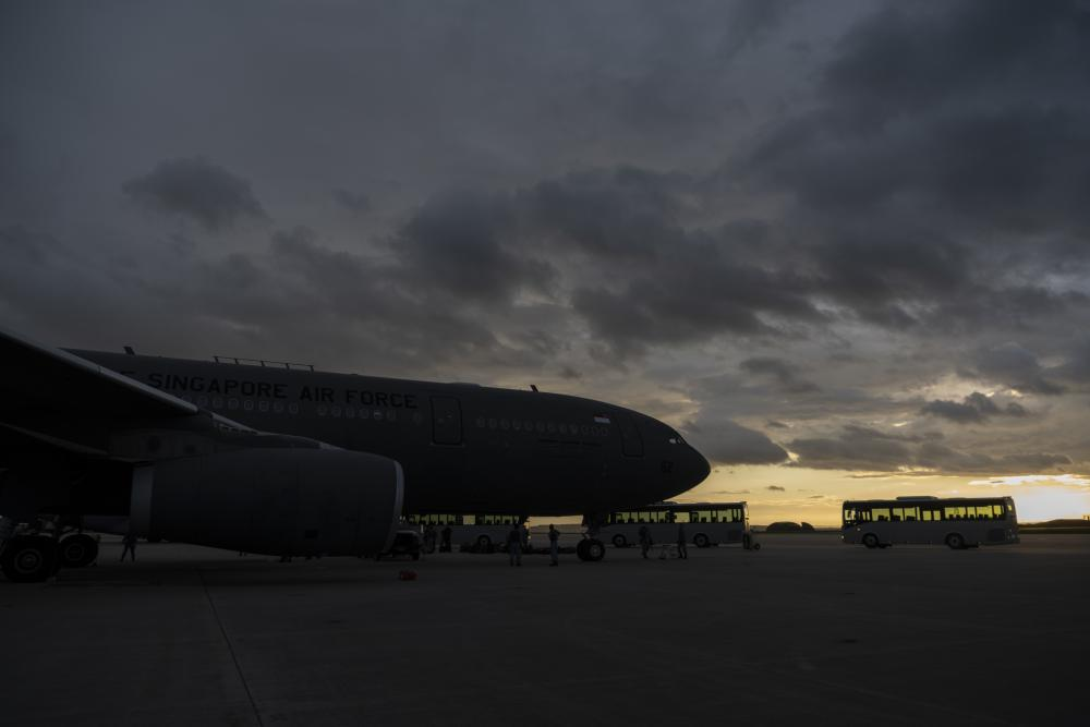U.S. Air Force buses wait to transport newly arrived members of the Singapore Armed Forces on the flightline of Spangdahlem Air Base, Germany, Aug. 27, 2021. The Singapore Armed Forces is working alongside partners like the United States in order to provide a safe and secure passage for displaced families and evacuees from Afghanistan. (U.S. Air Force photo by Tech. Sgt. Maeson L. Elleman)