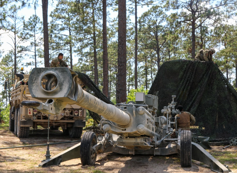 Soldiers with the Ohio Army National Guard's 1st Battalion, 134th Field Artillery Regiment, 37th Infantry Brigade Combat Team create new cover and concealment for their M777 howitzer June 16, 2021, at the Joint Readiness Training Center in Fort Polk, La.
