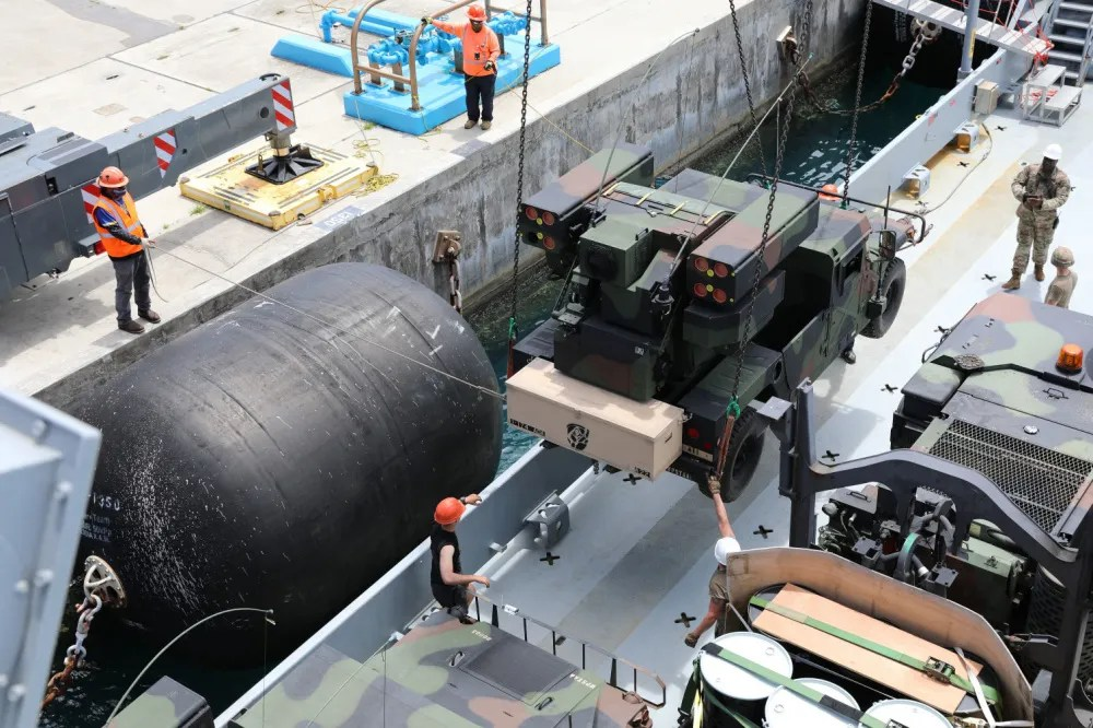 Soldiers of the 97th Transportation Company, 7th Sustainment Brigade, and civilian contract workers load an Avenger Air Defense System assigned to 1st Battalion, 174th Air Defense Artillery Regiment onto an Army Watercraft System in support of exercise Forager 21 on July 28, 2021, Naval Station Guam.