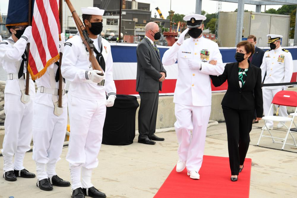 Gloria Valdez, ship's sponsor for the USS Vermont (SSN 792), is escorted by chief of the boat Senior Chief Petty Officer Robert Antrim as part of the official party for a commissioning commemoration onboard Naval Submarine Base New London in Groton, Conn., Aug. 28.