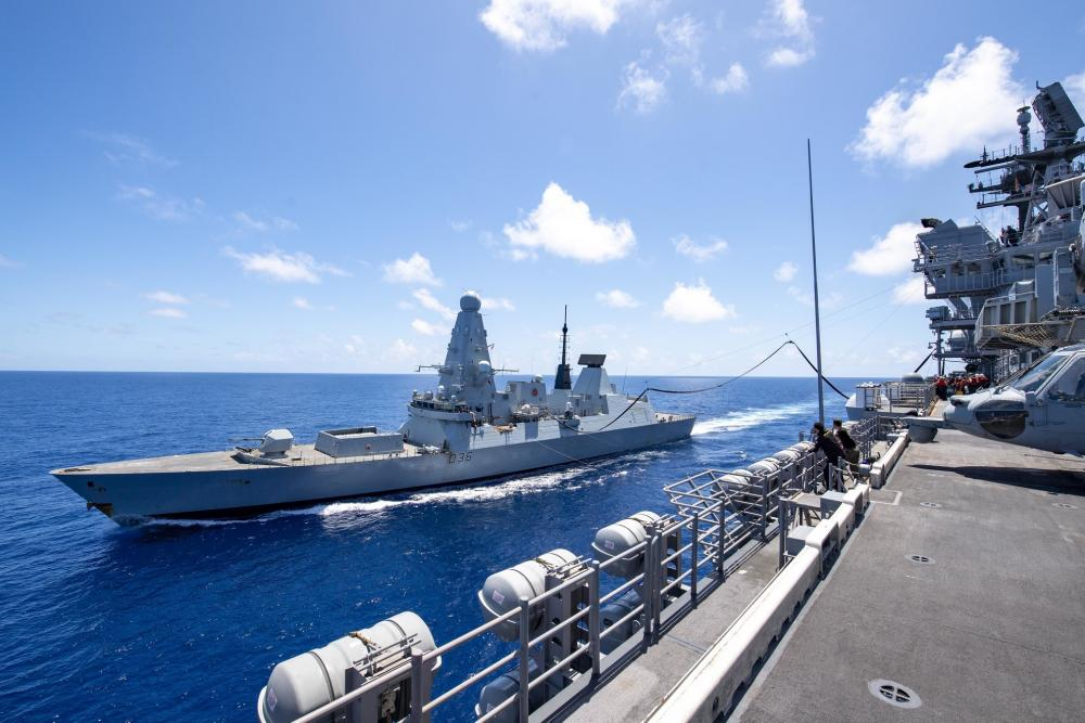 The Royal Navy Destroyer HMS Defender (D36) receives fuel from the forward-deployed amphibious assault ship USS America (LHA 6) during a fueling-at-sea.