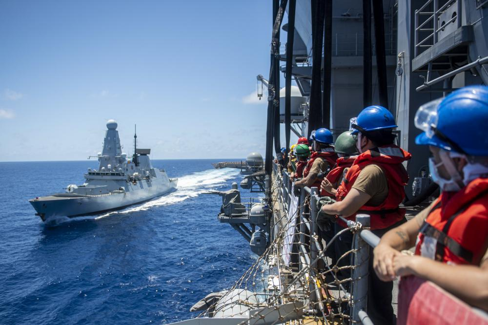 Sailors assigned to the forward-deployed amphibious assault ship USS America (LHA 6), man the rails before a fueling-at-sea with Royal Navy destroyer HMS Defender (D36).