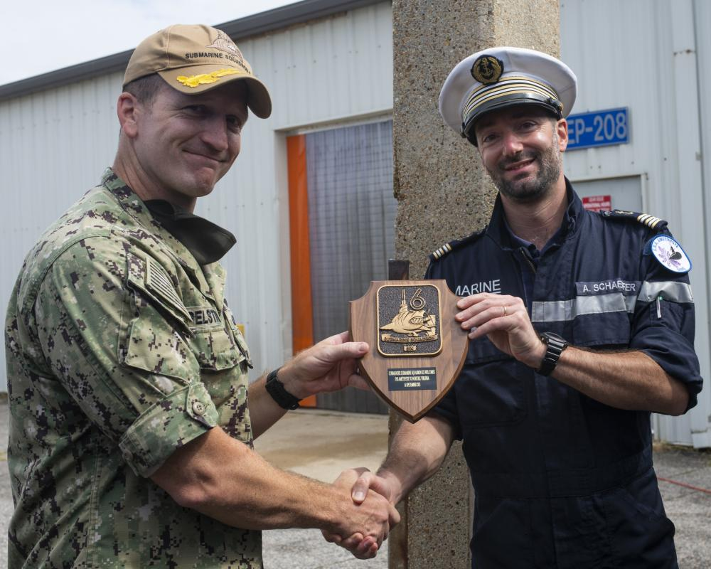 Capt. Jeremy Pelstring, assigned to Commander, Submarine Squadron 6, exchange gifts with Cmdr. Aymeric Schaeffer, commanding officer of the nuclear-powered French submarine FNS Amethyste (S605), at Naval Station Norfolk, Sept. 17, 2021