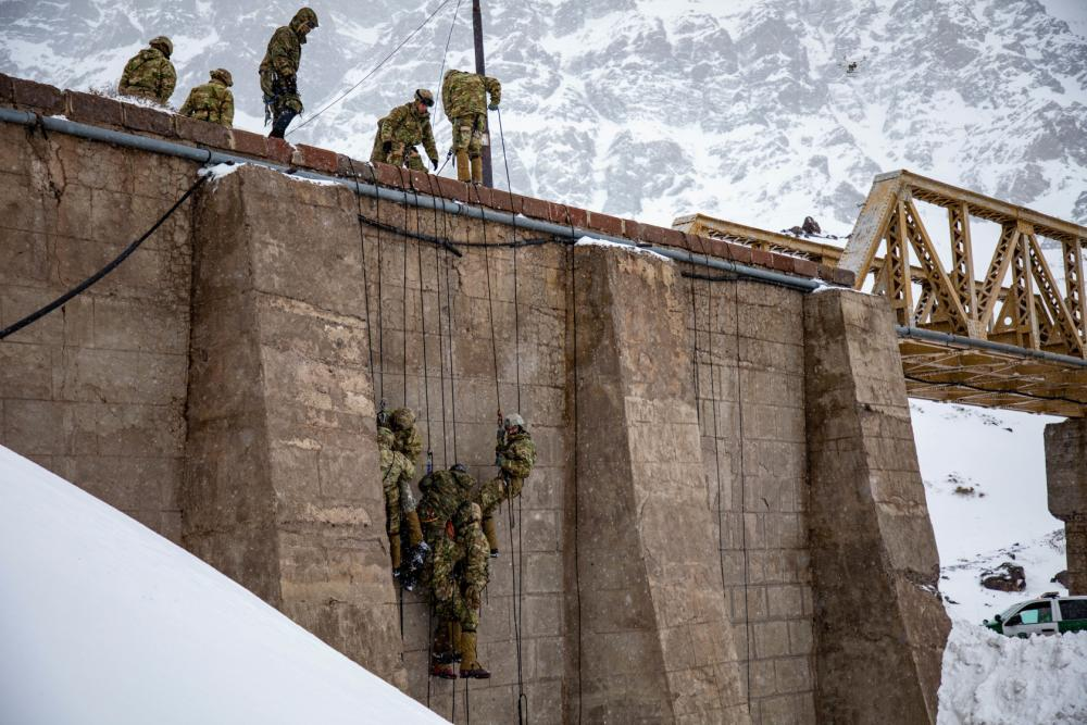 U.S. Army soldiers assigned to Bravo Company, 2nd Battalion, 87th Infantry Regiment, 2nd Brigade Combat Team, 10th Mountain Division, rappel off a bridge at the Chilean Army Mountain School in Portillo, Chile, Aug. 20, 2021.