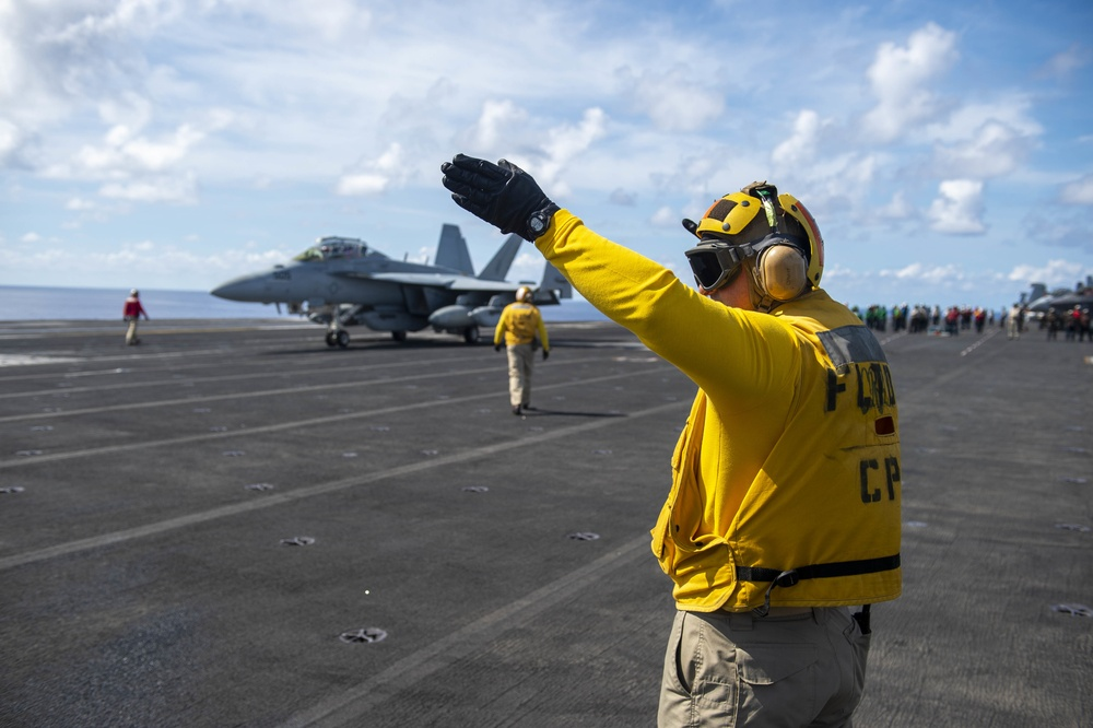 """A Sailor directs an EA-18G Growler, assigned to the """"Gauntlets"""" of Electronic Attack Squadron (VAQ) 136, from the flight deck of Nimitz-class aircraft carrier USS Carl Vinson (CVN 70)"""