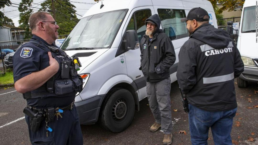 Eugene Police officer Bo Rankin, left, meets with Cahoots administrative coordinator Ben Brubaker and emergency crisis worker Matt Eads, right, after working a shift together as part of the Community Outreach