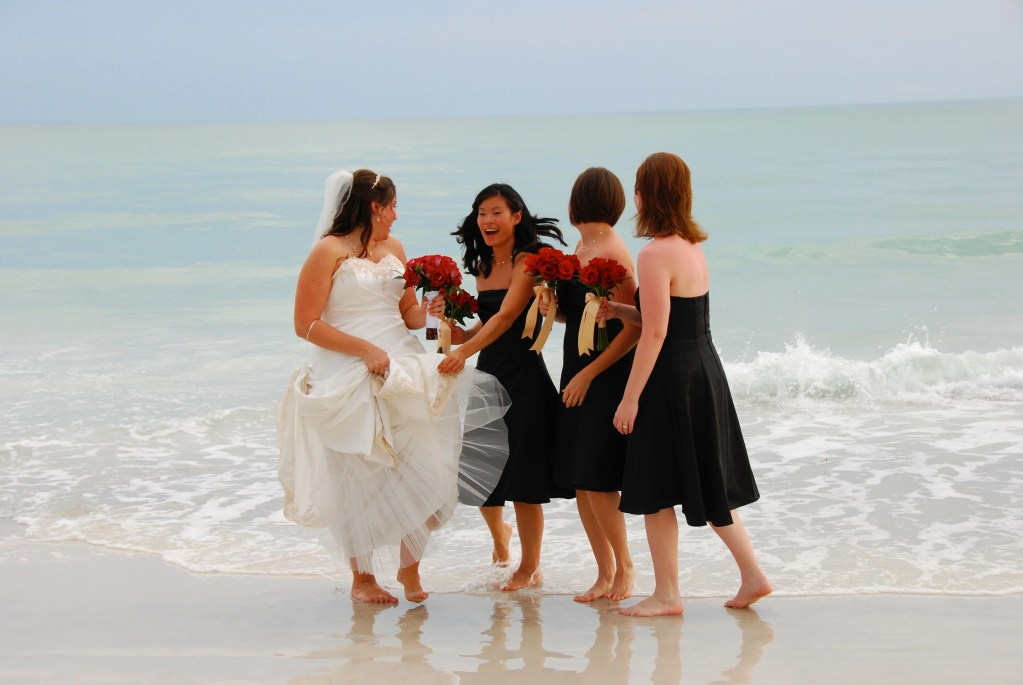 bride and brides may laughing as the ocean waves move toward them