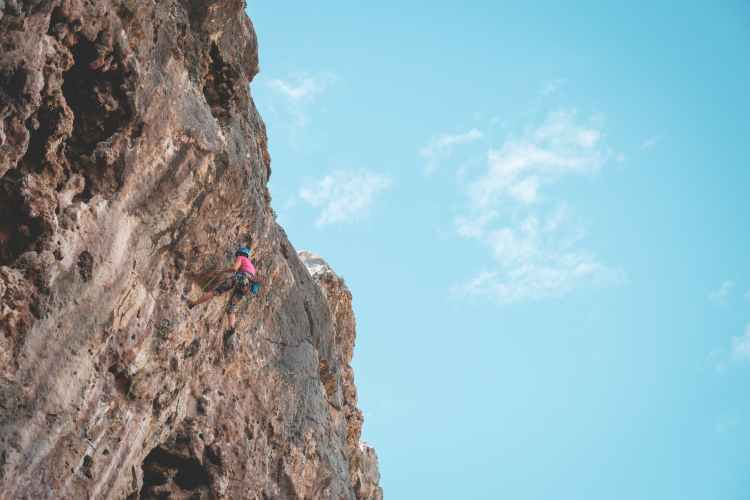 person climbing on rocky mountains under sunny sky with clouds