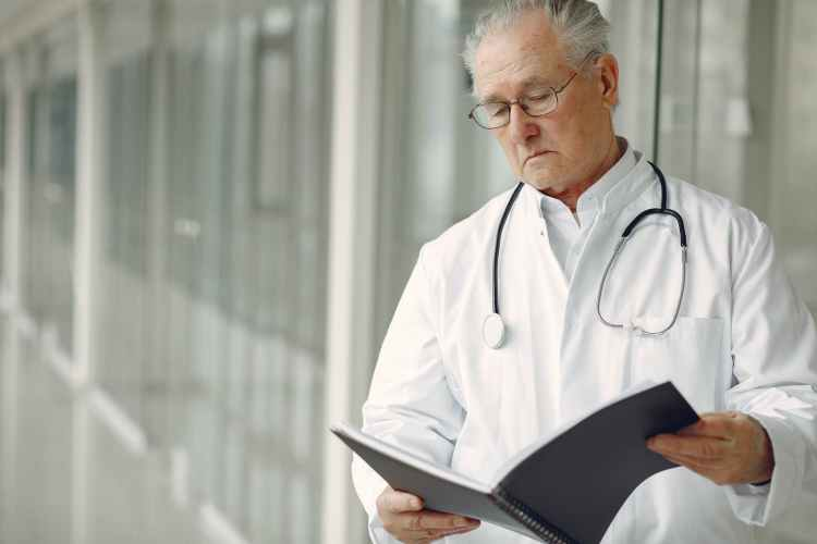 contemplative doctor in uniform reading clinical records