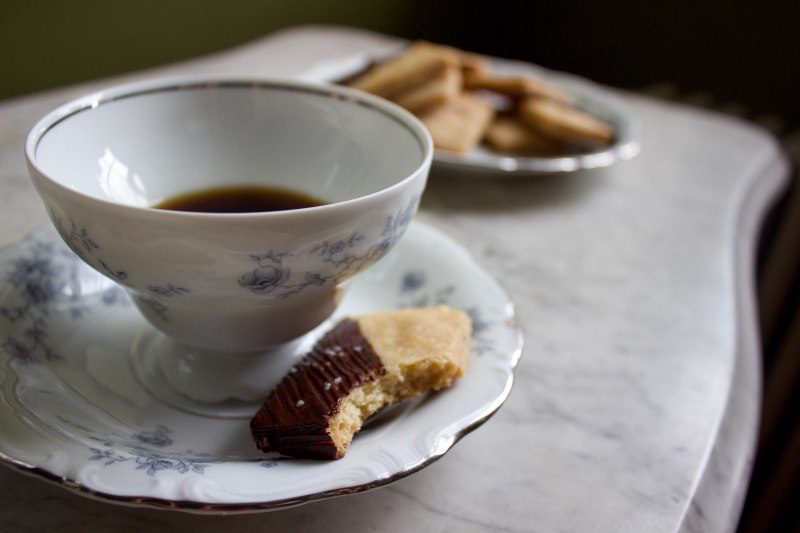 Chocolate dipped shortbread on the saucer of a tea cup full of coffee, a single bite taken out of the corner.