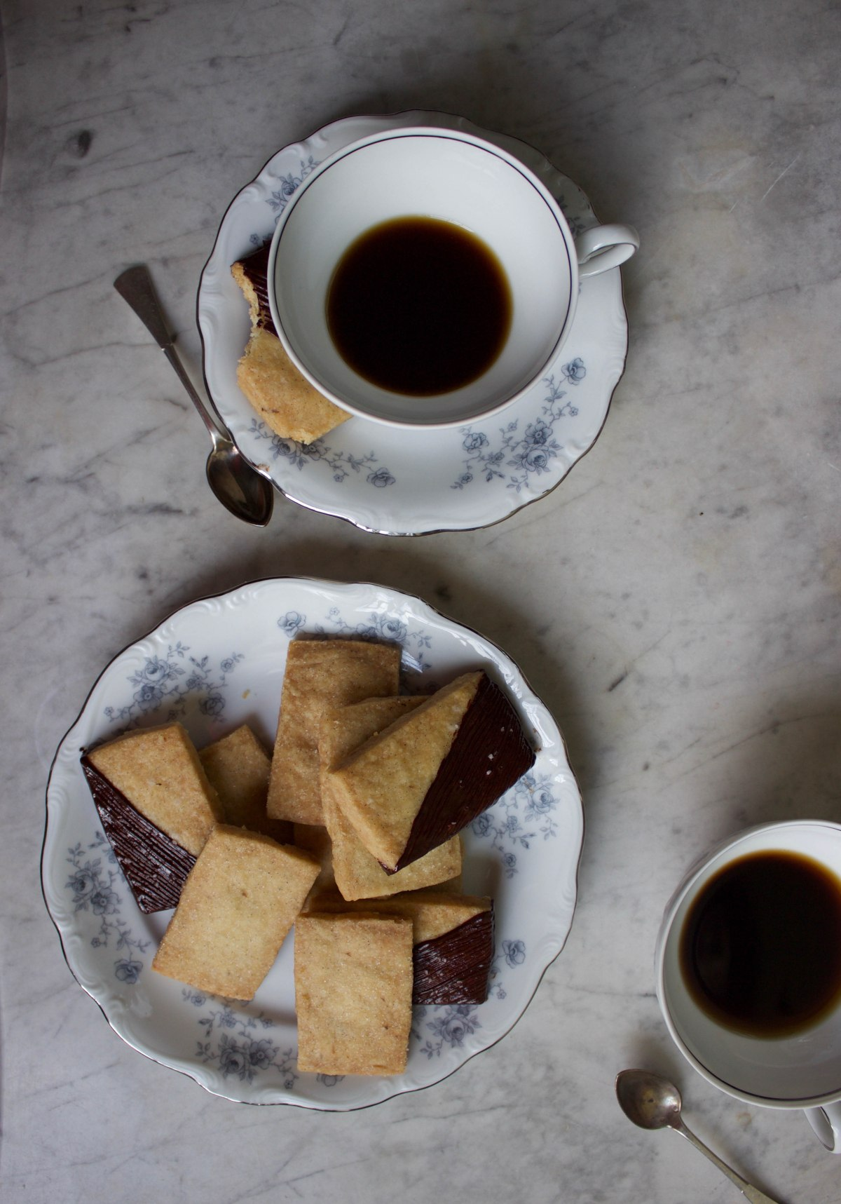 Black coffee in white and blue teacups and shortbread dipped in dark chocolate and sprinkled with sea salt.