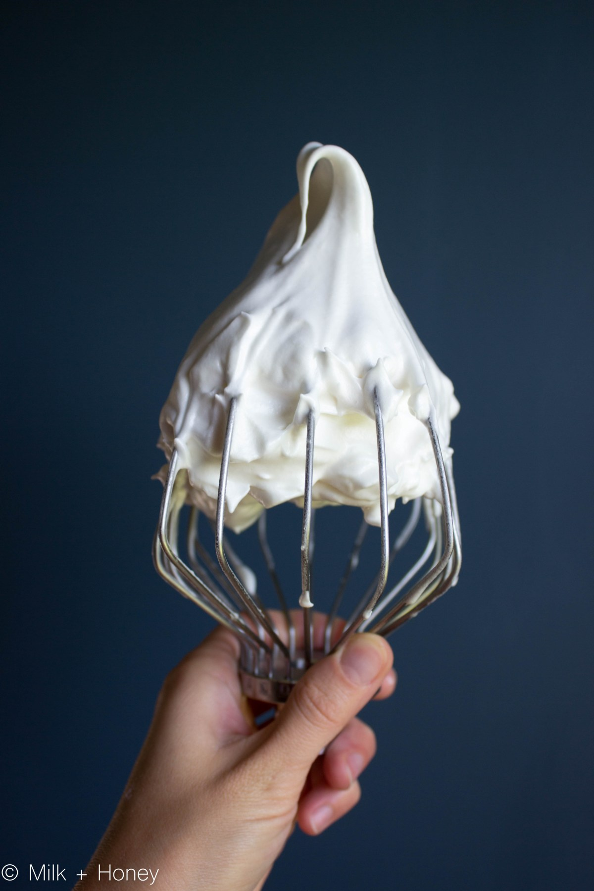 A hand holding a wire whisk, covered in meringue.