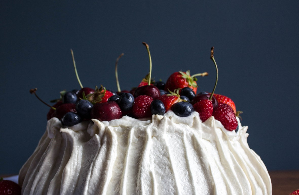 pavlova, covered in fresh fruit sitting on top of a blue napkin