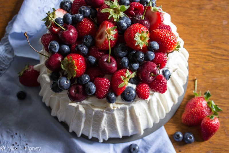 Pavlova, covered in fresh fruits, pictured from above.