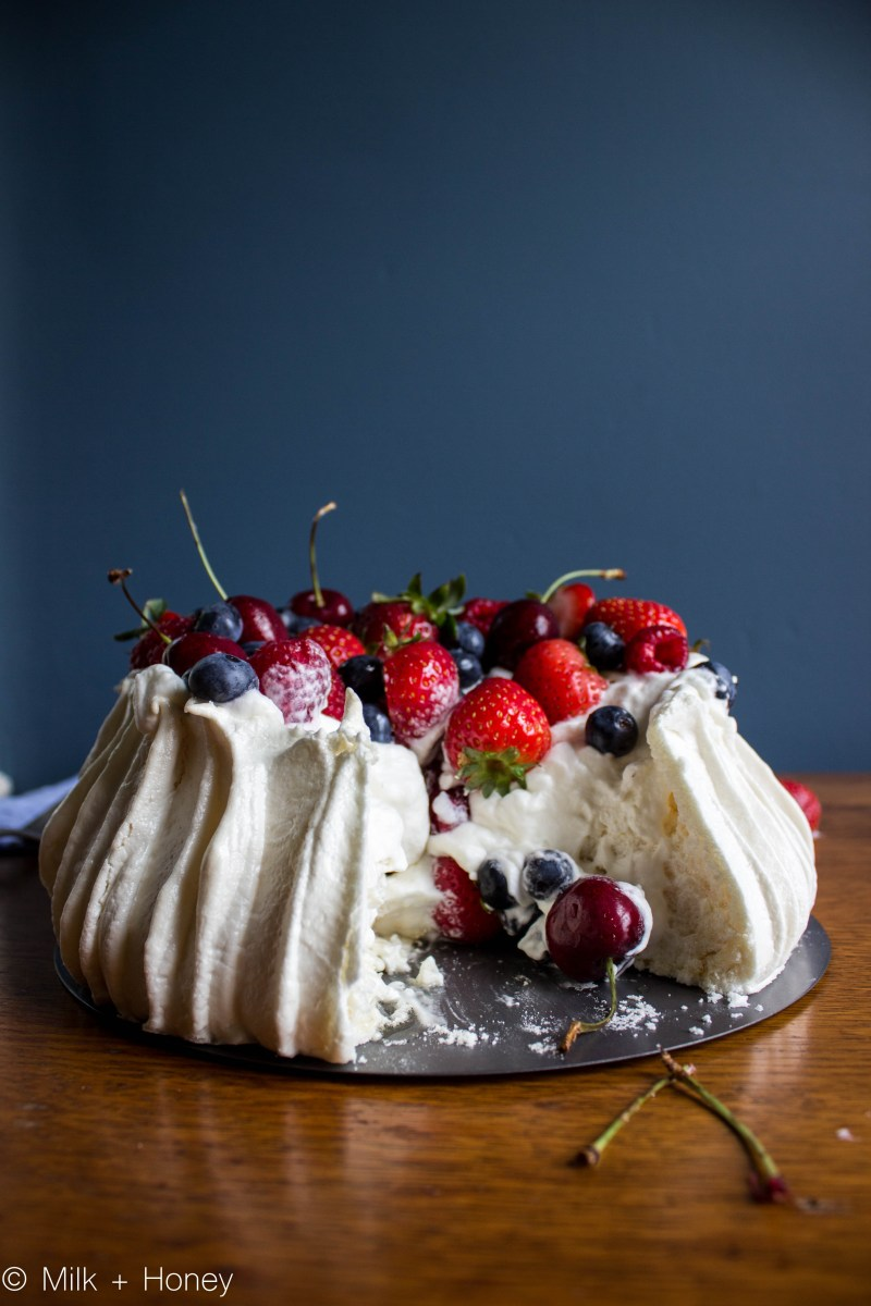 fresh fruit pavlova, pictured with a large piece cut out of it, fruit spilling down the center and onto the table
