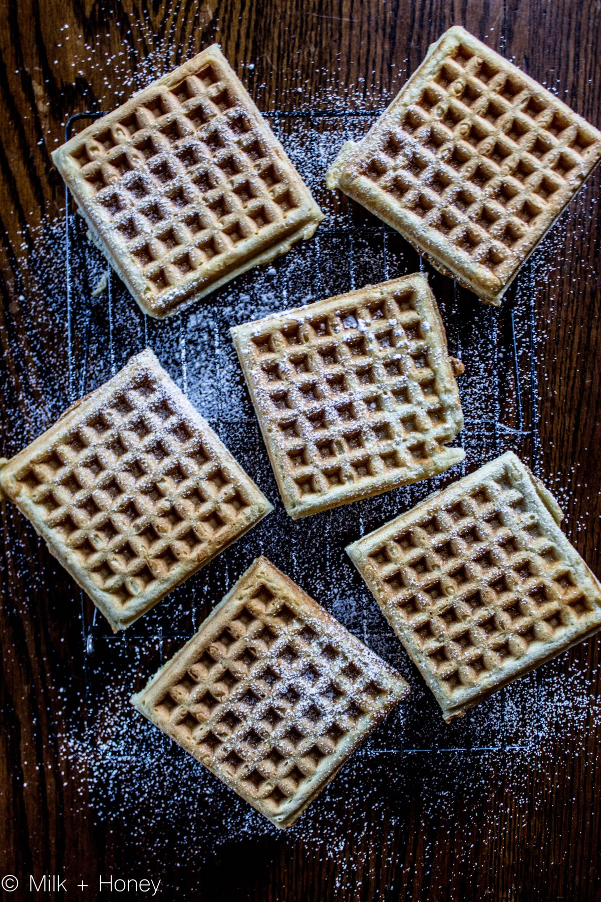 six waffles on a cooling wrack, dusted with powdered sugar, pictured from above