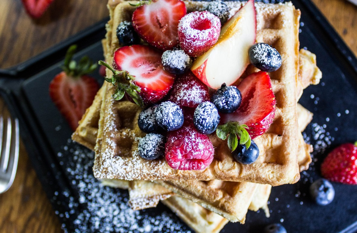 A stack of waffles pictured from above, covered in fresh berries and powdered sugar.