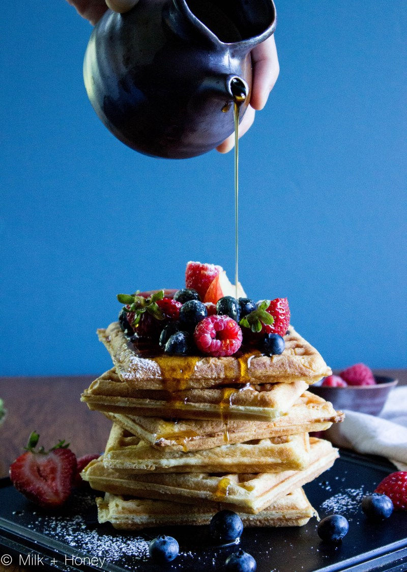 A stack of waffles covered in fresh berries and powdered sugar, a hand pours syrup over them.