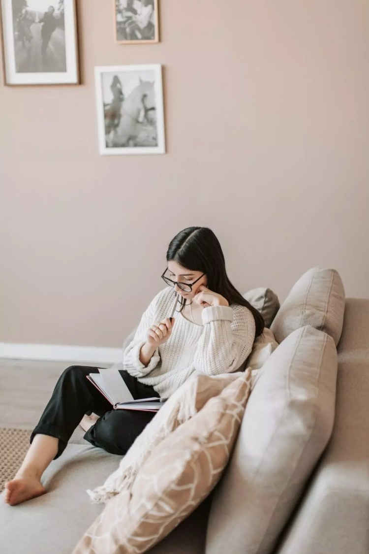 Thoughtful young female freelancer reading diary at home