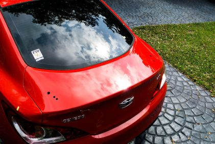 Spoiler holes drilled in the trunk of a 2010 Hyundai Genesis Coupe.