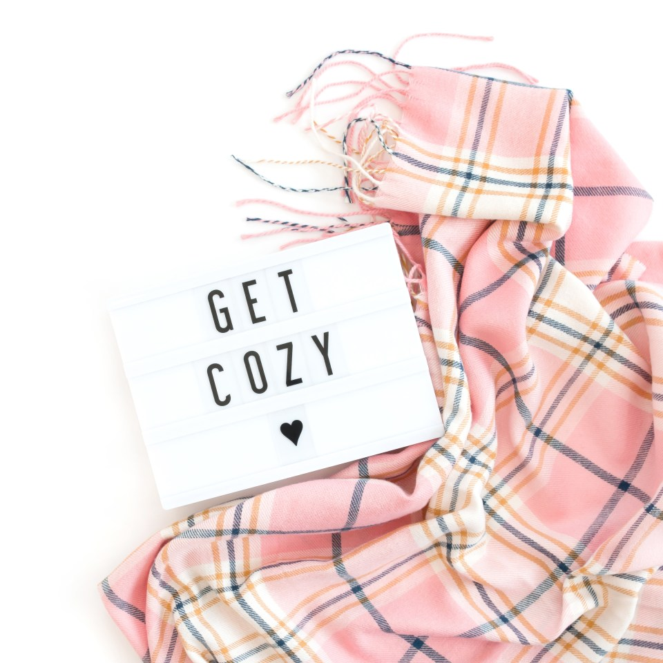 Pink plaid blanket and Get Cozy lightbox sign