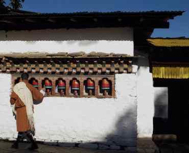 Paro, Bhutan, unidentified male pilgrim in traditional dress turning prayer wheels in Kyichu Lhakhang