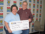 Michael McMillan and his wife happily hold his $2 million  jumbo check.