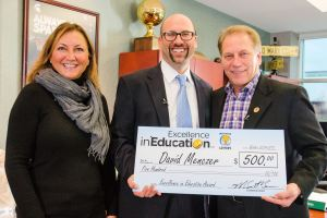 David Menczer (center) poses for a photo with his wife, Sandy Menczer and Michigan State University basketball coach Tom Izzo after accepting his Excellence in Education Award from the Michigan Lottery.