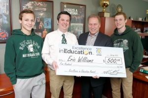 Eric Williams (second from left) poses for a photo with his nephews, Nick Dodge (left), Jack Dodge (right), and Michigan State University basketball coach, Tom Izzo, after accepting his Excellence in Education Award from the Michigan Lottery.