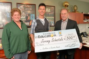 Jeremy Schnotala (center) poses for a photo with his friend and fellow educator, Kim Swiger, and Michigan State University basketball coach, Tom Izzo, after accepting his Excellence in Education Award from the Michigan Lottery.