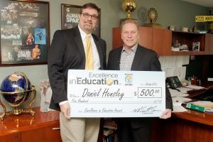 Daniel Hensley poses for a photo with Michigan State University basketball coach, Tom Izzo, after accepting his Excellence in Education Award from the Michigan Lottery.