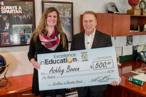 Ashley Bowen poses for a photo after accepting her Excellence in Education award from Michigan State University basketball coach Tom Izzo.