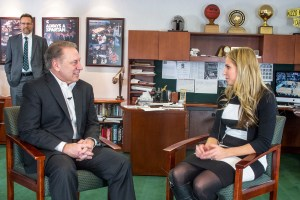 Trisha Wellock talks with Michigan State University basketball coach, Tom Izzo, after accepting her Excellence in Education award.