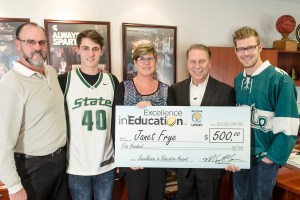 Janet Frye poses for a photo with (left to right) her husband, Dwayne, and sons Trevor and Kyle, after accepting her Excellence in Education award from Michigan State University basketball coach Tom Izzo.