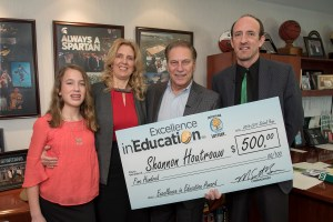 Shannon Houtrouw poses for a photo with his wife, Susan Houtrow, and daughter, Abigail Houtrow, after accepting his Excellence in Education award from Michigan State University basketball coach Tom Izzo.