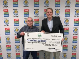 Michigan Lottery Commissioner, Aric Nesbitt, presents Stanley Wilson (left), with a check for his $25,000 a year for life Lucky For Life prize.