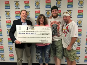 Lottery Commissioner, Aric Nesbitt (left), presents Club Keno The Jack winner, Rachel Signorello, with a check for $292,524 while her son, Tyler, and husband, Bob, look on.