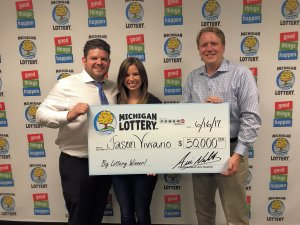 Lottery Commissioner, Aric Nesbitt, presents Jason Viviano (left) and his wife, Jacqueline, with a check for $50,000.